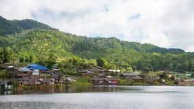 Vila pequena ao lado do lago e da montanha fotos de stock royalty free