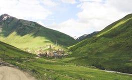 Vila pequena no Cáucaso com as torres de pedra da defesa ao lado de um rio em um vale Ushguli em Ge foto de stock