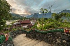 Vila tradicional do lao com escadas do templo e fundo da montanha perto de Vang Vieng imagem de stock royalty free