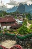 Vila tradicional do lao com escadas do templo e fundo da montanha perto de Vang Vieng foto de stock royalty free