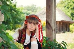 Vila ucraniana Menina no traje nacional do hutsul que senta-se com fruto Fotografia de Stock