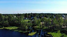 Vilage acogedor del verano de la visión aérea en orilla del lago almacen de metraje de vídeo