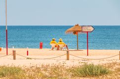 Lifeguard dressed in yellow sitting on a chair on the beach royalty free stock photo