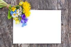 Vildblommabukett på ekbrunttabellen med det vita arket av PA Royaltyfria Foton