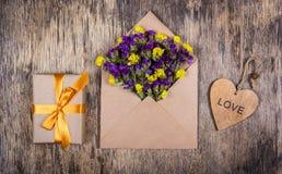 Vildblommor i ett kuvert, en ask med en guld- pilbåge och hjärta Festligt begrepp Royaltyfri Foto