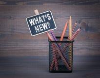 Vilken nya ` s En liten svart tavlakrita och en färgad blyertspenna på wood bakgrund Arkivfoto