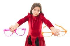 Vilket är bättre hårt val Tillbehör för ungehållglasögon Barn isolerad vit bakgrund Flickan väljer stort roligt arkivbild
