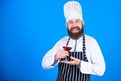 Vilket vin som tjänar som med matställen Sommelieren tycker om vin Utmärkt smak Kocken i kockhatt och förklädet förbättrar sommel royaltyfri fotografi
