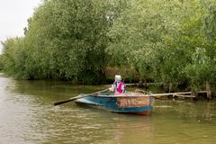 Fisherwoman manages a boat with oars on Danube River. Vilkovo, Ukraine - May, 26, 2018: Fisherwoman manages a boat with oars on Danube River Royalty Free Stock Photography