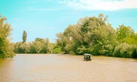 River landscape with a pleasure boat on the Danube River. Vilkovo, Ukraine - May, 26, 2018: River landscape with a pleasure boat on the Danube River stock images