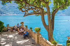Villa Balbianello, Como lake, Italy. VILLA BALBIANELLO, ITALY - AUGUST 02, 2015: Tourists sitting in the park of villa Balbianello with view of Como lake, Italy royalty free stock photos