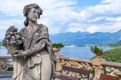 Villa Balbianello yard with beautiful statue. Of a woman. Lake Como, mountains and blue sky on background. Sunny day. Italy beauties stock photo