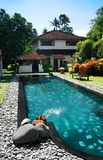 Villa in Bali resort. A photograph image of a large luxury holiday villa house in the grounds of a tropical balinese resort on Sanur beach, with a blue swimming Stock Photos
