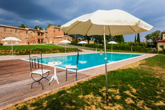 Villa. A beautiful and luxurious tuscany swimming pool with parasols and chairs Stock Photo