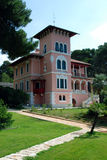 Villa Carolina in Cikat in Mali Losinj,Croatia. Pink villa Carolina in Mali Losinj with the green garden and palm trees Stock Photos