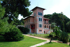 Villa Carolina in Cikat in Mali Losinj,Croatia. Pink villa Carolina in Mali Losinj with the green garden and palm trees Royalty Free Stock Photos