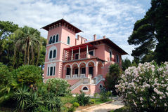Villa Carolina in Cikat in Mali Losinj,Croatia. Pink villa Carolina in Mali Losinj with the green garden and palm trees Royalty Free Stock Photo