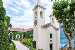 Villa del Balbianello green garden. With chapel. Clouds on background. Lenno, Italy royalty free stock image