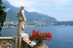 Villa del Balbianello. Red flowers and a statue in the garden of Villa del Balbianello - Lenno, Tremezzina, Como, Lombardy, Italy royalty free stock image