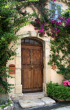 Villa Doorway, France. Richly-grained wooden door to private stucco villa in medieval village of Mougins, France.  Flowering vines frame the doorway, and there's Stock Photography