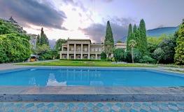 Villa a due piani leggera elegante con un prato inglese, un grande stagno blu circondato dagli alberi verdi alti contro il contes fotografia stock libera da diritti