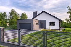 Villa with fence and garage. Stylish villa with fence, garage and lawn, exterior view royalty free stock images