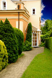 Villa and garden. Path to the entrance door of a villa surrounded by a beautiful garden Stock Image