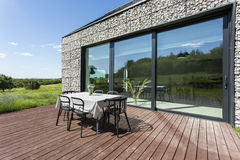 Villa patio with stone walls. Villa patio with wooden flooring, simple dining set, exterior stone walls and big windows Stock Images