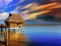 Villa on piles on water at the time sunset Stock Image