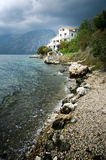 Villa at the seaside. Rocks on the beach and stormy clouds, mountains on the background Stock Photography