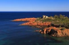 Villa sulla linea costiera rossa del Mediterraneo della roccia Fotografia Stock