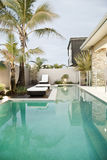 Villa and swimming pool. Luxurious tropical villa with palm trees and outdoor swimming pool