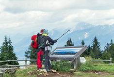 Villach,  Austria – August 11, 2016: Young couple tourist hiking together in the Austrian Alps. Royalty Free Stock Images