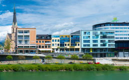 Villach - May 2016, Austria: Old Church and modern buildings on bank of the river Drava in central part of the city Royalty Free Stock Photography
