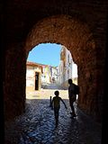 Village in Algarve, Portugal. Tourists entering in a village in Algarve trough the medieval wall.The Algarve is the southernmost region of Portugal. Tourism and royalty free stock photo