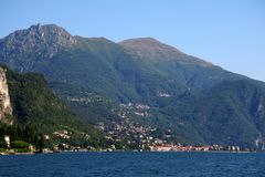 Village along Lake Como, Italy. A hillside village in the Italian Alps on Lake Como, Italy.  Large mountains loom in the background and show the small scale of Stock Photo