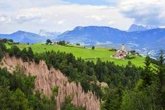 Village alpin de paysage de vue de fond sur un plateau entouré par des montagnes Rennon dans le Tirol Photos libres de droits