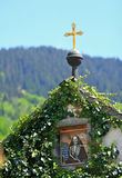 Village In The Alps. Small golden cross sitting a top of gate.Church in Ramsau.Germany Alps,Bavaria stock photography