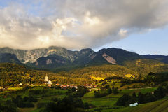 Village in the Alps. Sun in the valley. Beautiful village with church in the Julian Alps, Slovenia Stock Image