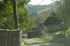 Village in Apuseni Mountains, Romania. Wooden homes and fences along path in traditional village of the Apuseni Mountains in Transylvania, Romania Royalty Free Stock Images
