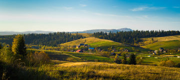 Village and autumn forest in mountains panorama. Stock Images