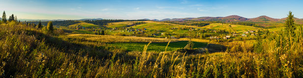 Village and autumn forest in mountains panorama. Royalty Free Stock Images