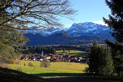 Village aux collines des Alpes au printemps Images stock