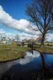Village avec le ciel bleu se reflétant dans l'étang Images libres de droits