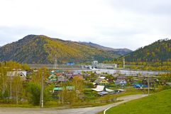 The village on the background of the autumn forest, mountains and hydro-power. Russia royalty free stock photos