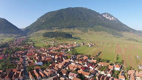Village at the base of a mountain ridge, aerial view stock video