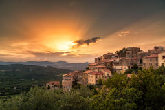 Village of Belgodere in Corsica lit by dramatic sunset. Ancient hilltop village of Belgodere in the Balagne region of Corsica lit up by a dramatic evening sunset Royalty Free Stock Photos