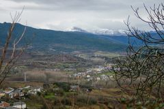 Beautiful village of Bierzo surrounded by snowy mountains and a cloudy sky. Village of the Bierzo valley surrounded by vegetation with snowy mountains in the stock photos