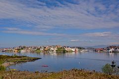 The village of Bjørnøy on an island in Norway. Bjørnøy village on an island, view from across the Beach of Hundvåg with people relaxing on the Stock Photography