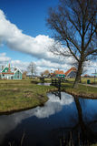 Village with blue sky reflecting in pond. Dutch traditional village with pond in foreground. Blue skies and fluffy clouds that are reflected in the water. Image Royalty Free Stock Images